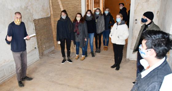 Der Architekt Stephan Dreier führt kleine Gruppen von Studierenden durch das in der Sanierung befindliche Kutschenhaus.